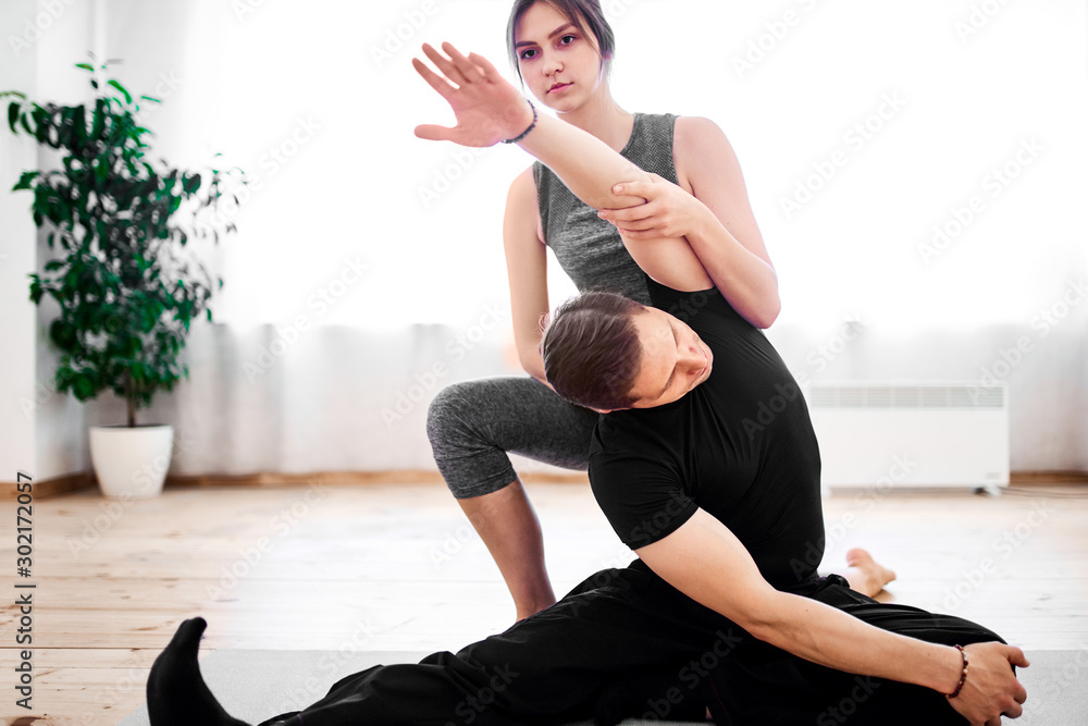 Fototapety, obrazy: Man doing yoga with woman trainer.