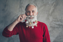 Closeup Photo Of Funny Old Santa Claus Man Colorful Toy Balls In Long Beard X-mas Decorations After Salon Wear Red Pullover Hipster Outfit Isolated Grey Concrete Wall Background