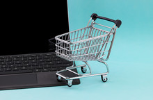 Internet Shopping Concept Of A Laptop Computer With A Mini Shopping Cart Basket Resting On The Keyboard Isolated Against An Green Background