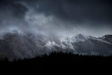 Stunning Dramatic Landscape Image Of Snowcapped Glyders Mountain Range In Snowdonia During Winter With Menacing Low Clouds Hanging At The Peaks