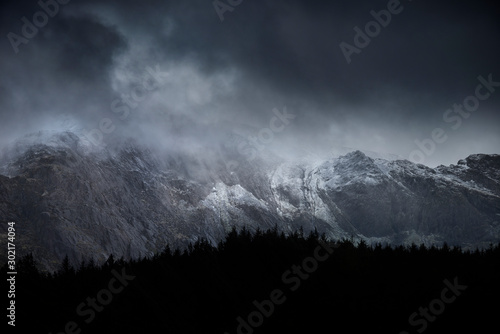 Foto auf AluDibond Grau Verkehrs Stunning dramatic landscape image of snowcapped Glyders mountain range in Snowdonia during Winter with menacing low clouds hanging at the peaks