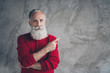 canvas print picture - Photo of amazing aged grandpa indicating finger empty space advising new product wear red knitted pullover hipster santa role isolated grey color concrete wall background
