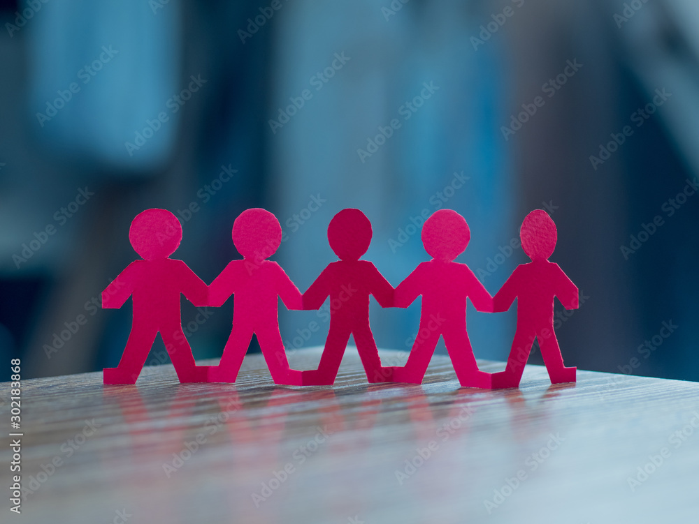 Fototapeta Team of paper chain people in a row on blurred background holding hands