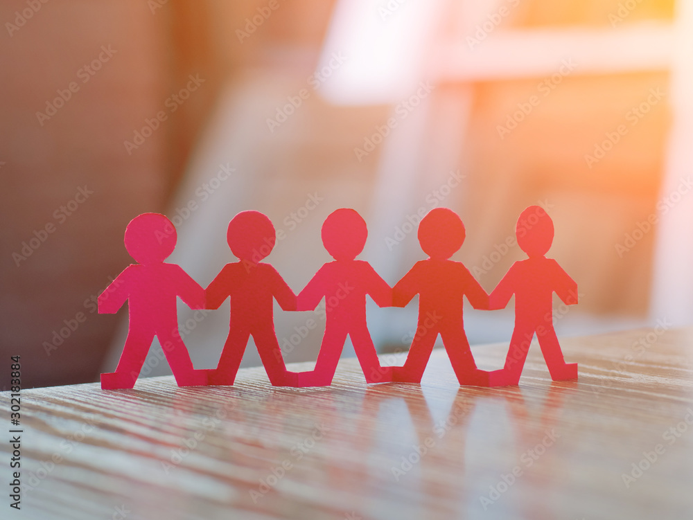 Team of paper chain people in a row on blurred background holding hands