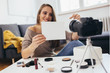 young woman influencer holding blank cardboard while reviewing make-up products,