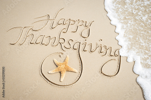 Happy Thanksgiving message handwritten on smooth sand beach with decorative starfish and oncoming wave - 302191800