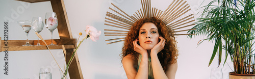 panoramic shot of woman with accessory on head propping face with hands on grey