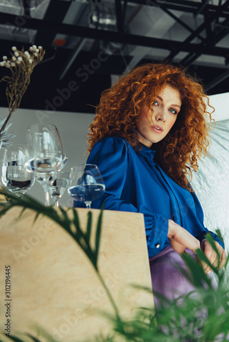 beautiful redhead girl looking at camera near glasses with water - 302196445