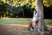 木に寄りかかる女の子