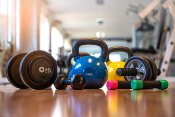Exercise weights - dumbbell with extra plates , kettlebells, Ab roller wheels on a floor in center fitness