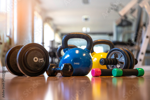 Exercise weights - dumbbell with extra plates , kettlebells, Ab roller wheels on a floor in  center fitness - 302200073