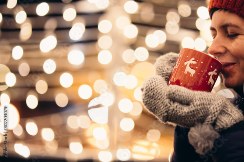 Christmas light and a woman holding in hand a red mug with hot drink Fototapet