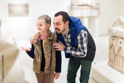 Father and daughter looking at ancient bas-reliefs in museum Canvas Print
