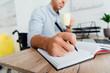 Selective focus of man in wheelchair holding cup and writing in notebook at desk