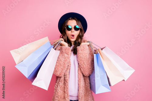 Photo of pretty millennial lady carry many packs shopper tourism abroad look unbelievable sales low prices mall wear fluffy jacket sun specs blue hat isolated pink background