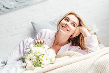 Selective Focus Of Cheerful Young Woman Lying Near Flowers On Bed