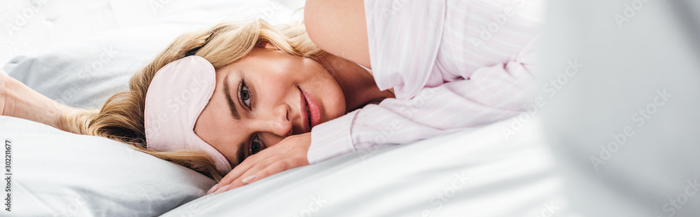 Fototapeta panoramic shot of cheerful woman with eye mask lying on bed at home