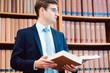 canvas print picture - Anwalt in der Bibliothek seiner Kanzlei liest in der juristischen Fachliteratur nach