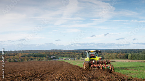 tractor and plow under blue sky on field in luxembourgh Wallpaper Mural
