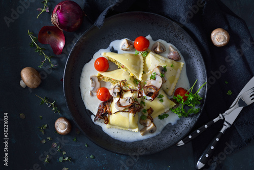 Obraz Schwäbische Gemüse-Maultaschen mit Champignonrahmsoße und Röstzwiebeln - Swabian vegetable ravioli with mushroom cream sauce and roasted onion rings, dark and moody style - fototapety do salonu