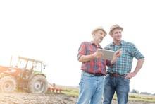 Senior Farmer Using Digital Tablet And Showing Farm To Mature Farmer