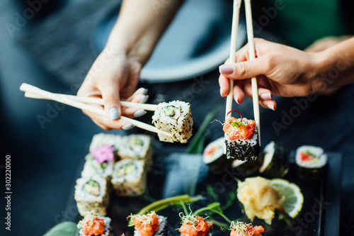 Fototapeta Chopstick holding sushi rolls set with salmon and cream cheese and cuccumber on black plate. Close Up. Uramaki, nori maki or futomaki sushi with trout fillets, soy sauce and wasabi. obraz