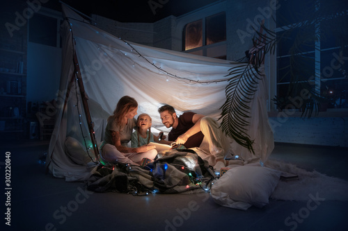 Photo  Caucasian family sitting in a teepee, reading stories with the flashlight in dark room with toys and pillows