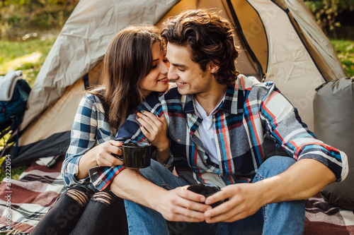 Foto auf Leinwand Rosa dunkel Young beautiful couple in casual dress sitting in a campsite near the tent. Attractive woman and handsome man spend time together sitting on plaid in nature