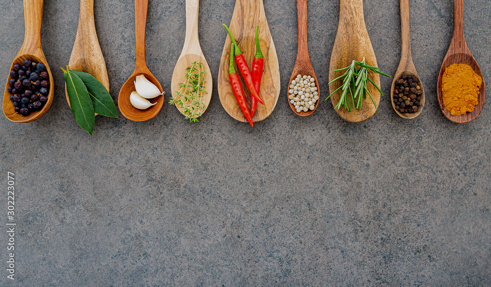 Fototapety, obrazy: Various of spices and herbs in wooden spoons. Flat lay spices ingredients chili ,peppercorn, rosemary, thyme on dark stone background.