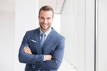 Young Attractive Businessman Standing With Arms Crossed In Office