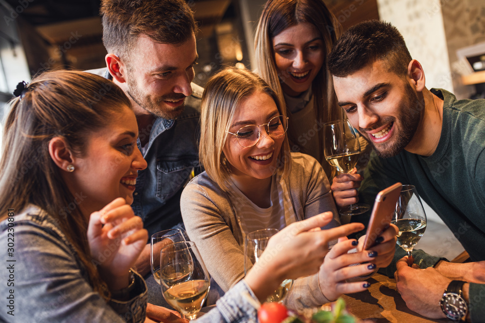 Fototapeta Group of young friends having fun in restaurant talking, laughing while dining at table and making selfie.