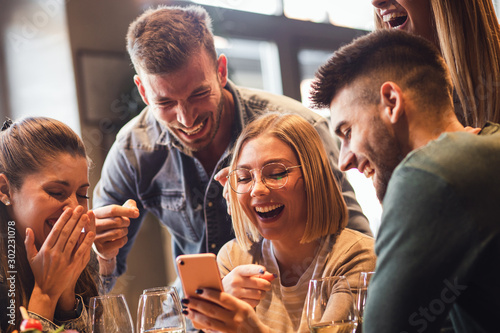 Obraz na płótnie Group of young friends having fun in restaurant talking, laughing while dining at table and making selfie