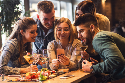 Obraz Group of young friends having fun in restaurant talking, laughing while dining at table and making selfie. - fototapety do salonu
