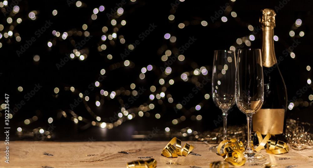 Fototapeta New Year's Eve background with champagne bottle and glasses confetti and gold snakes New Year's Eve background with confetti and gold snakes on wooden table, lights