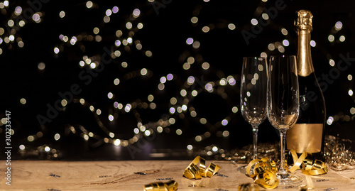 Poster de jardin Alcool New Year's Eve background with champagne bottle and glasses confetti and gold snakes New Year's Eve background with confetti and gold snakes on wooden table, lights