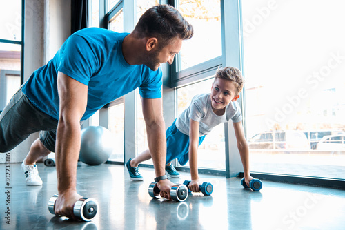 Foto  happy father looking at cheerful son and exercising with dumbbells