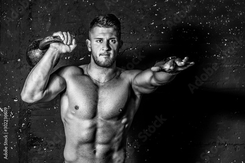 Fotografering Young strong sweaty focused fit muscular man with big muscles holding heavy kett
