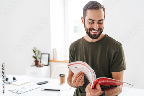 Image of caucasian happy man reading brochure and smiling