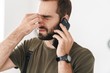 Image of caucasian tired man with headache talking on cellphone