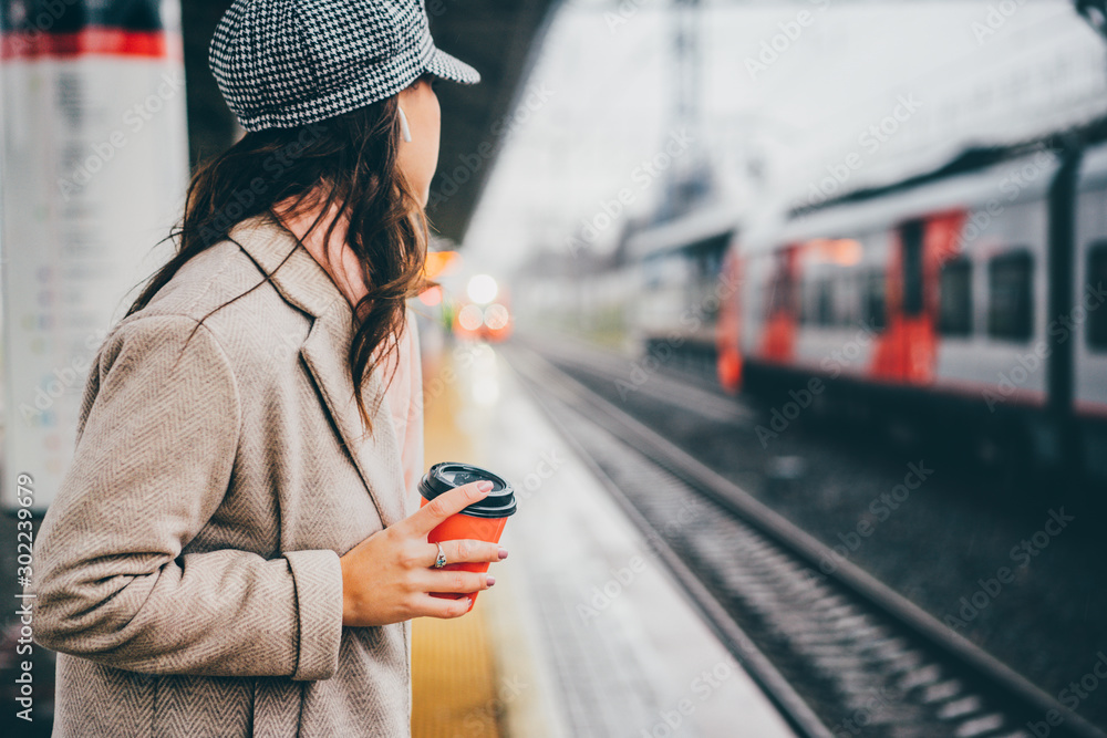 Fototapeta Woman holding red cup and drinking coffee during waiting the train at the station.