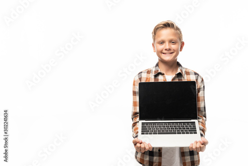 Fotografía  cheerful boy showing laptop with blank screen while smiling at camera isolated o