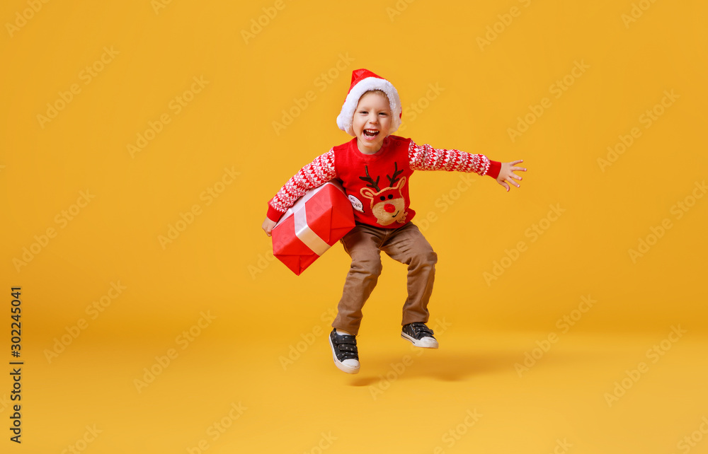 Fototapeta happy funny child boy in red Christmas reindeer costume jumping  with gift on yellow   background.