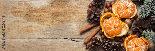 Tangerines, Christmas tree branches, cones, spices on a wooden background. Сoncept of New Year and Christmas, Christmas drink Mulled wine. Flat lay, top view. Banner
