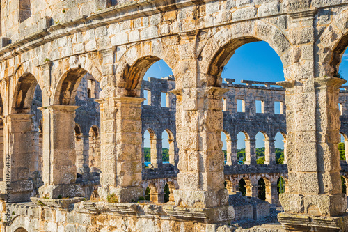 Photo sur Aluminium Con. Antique Ancient heritage in Pula, Istria, Croatia. Arches of monumental ancient Roman arena. Detail of historic amphitheater, wide angle view of high walls on blue sky background.