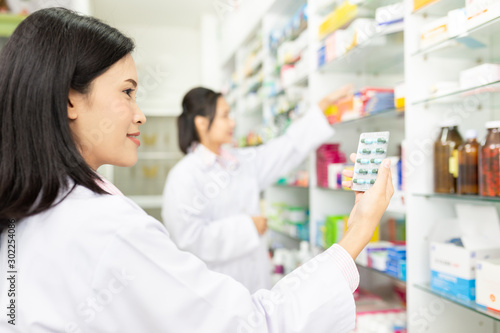 Photo asian female pharmacist check medicine stock in drugstore,she holding drug strip