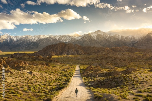 Fotomural  Lonely person walking on a pathway in Alabama hills in California with Mount Whi