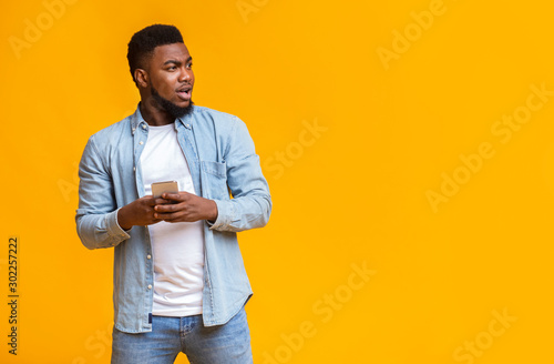Surprised man holding smartphone and looking aside at copy space Fototapet