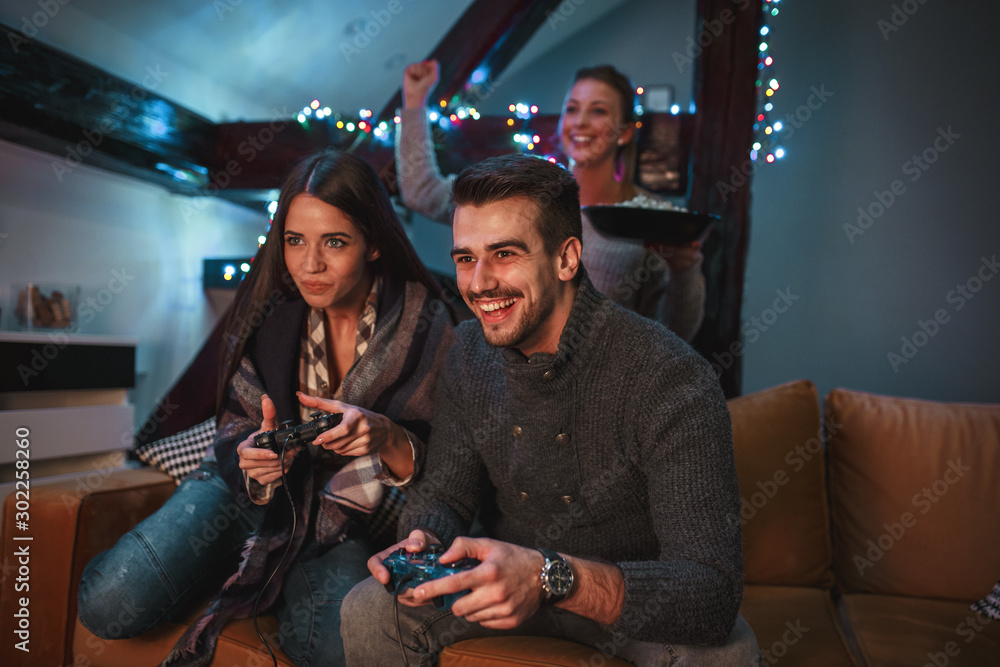 Fototapeta Group of best friends sitting at home on pleasant evening and playing games on console.They challenge each other to win .