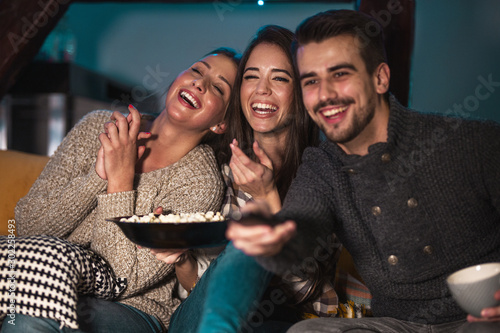 Group best friends sitting at home on pleasant evening and watching a comedy movie Wallpaper Mural