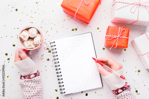 Fotomural Woman writing New Year greetings in notebook on background